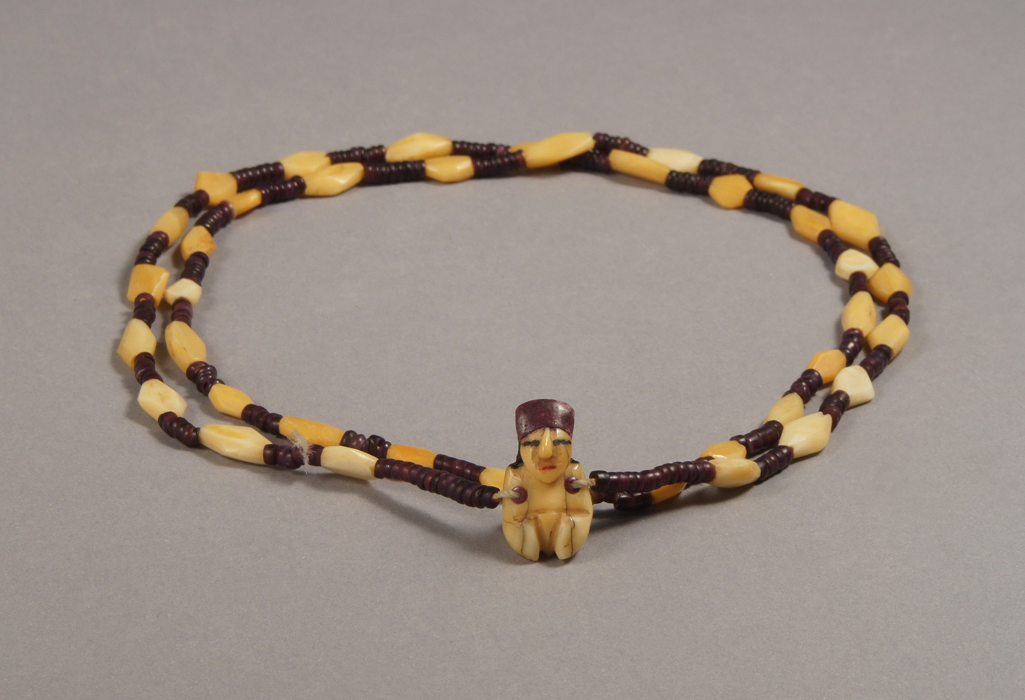Peru, Nazca necklace with bone and syondylus beads and a minature female pendant Bone